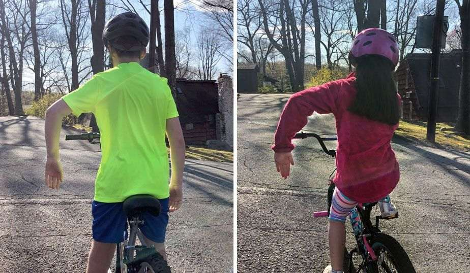 boy and girl using the STOP hand signal on their bikes