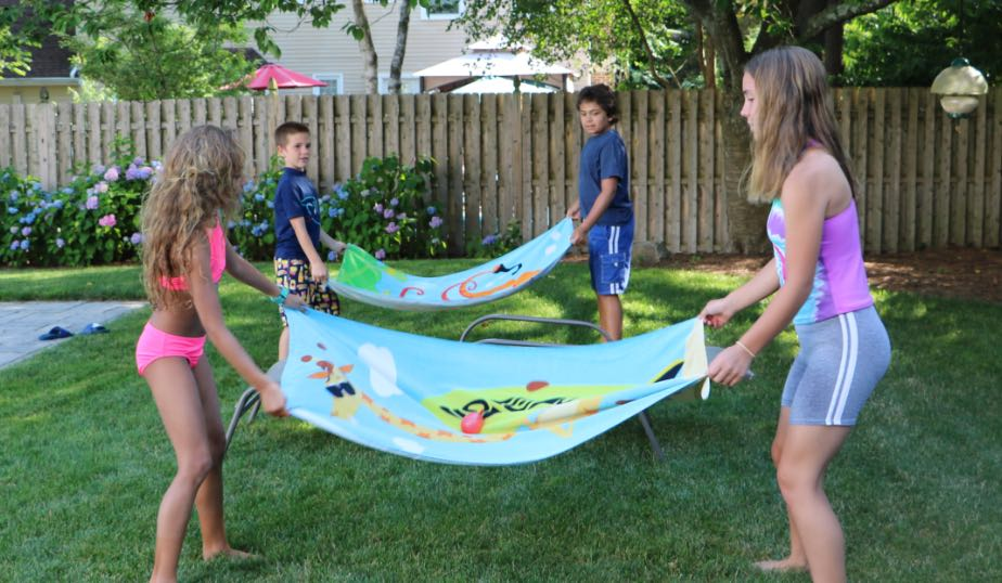 young children getting ready to toss the water balloons in an outdoor game for kids