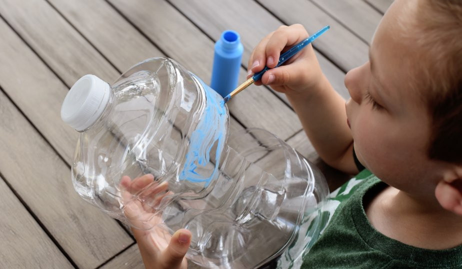 child painting a plastic water jug for the diy bird feeder activity for kids