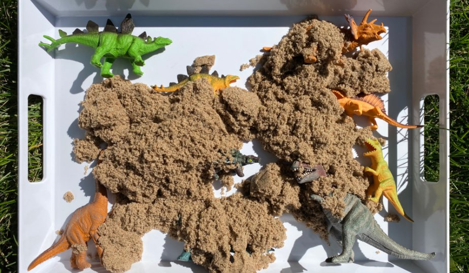 dinosaur figures covered in kinetic sand for dino discovery box diy for kids