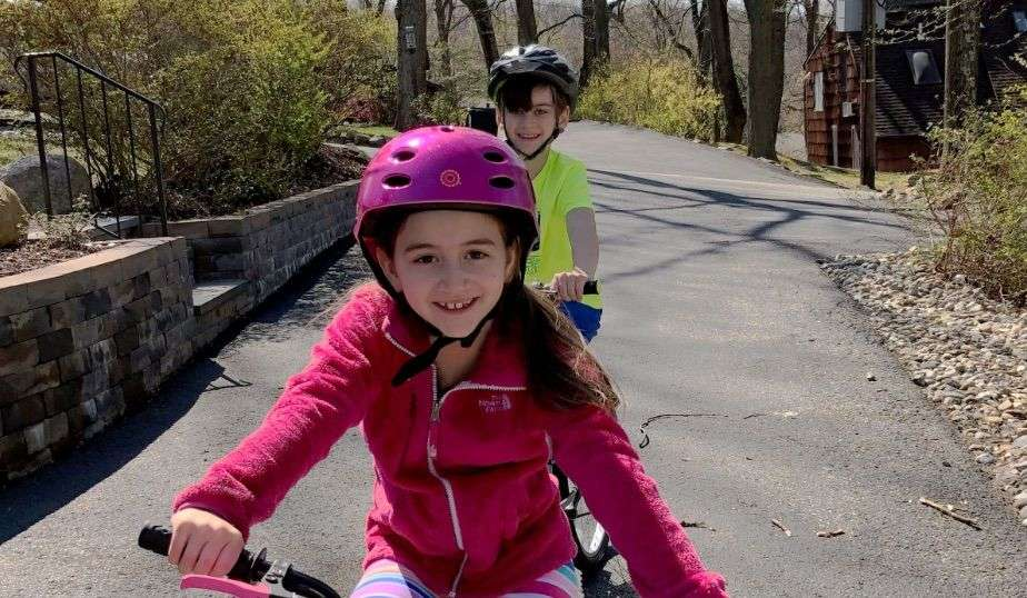 girl and boy with helmets safely ride their bikes